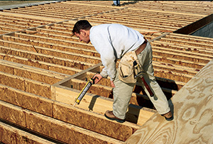 Worker gluing plywood flooring to I-joist